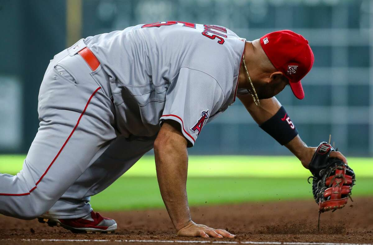 Los Angeles Angels first baseman Albert Pujols (5) stretches to make an out against the Houston Astros during the fifth inning of an MLB game at Minute Maid Park on Saturday, April 24, 2021, in Houston.