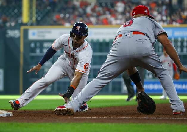 Houston Astros second baseman Robel Garcia (9) slides back to first base safely after a ball hit by center fielder Myles Straw (3) was caught by Los Angeles Angels right fielder Scott Schebler (44) during the sixth inning of an MLB game at Minute Maid Park on Saturday, April 24, 2021, in Houston. Photo: Godofredo A Vásquez/Staff Photographer / © 2021 Houston Chronicle