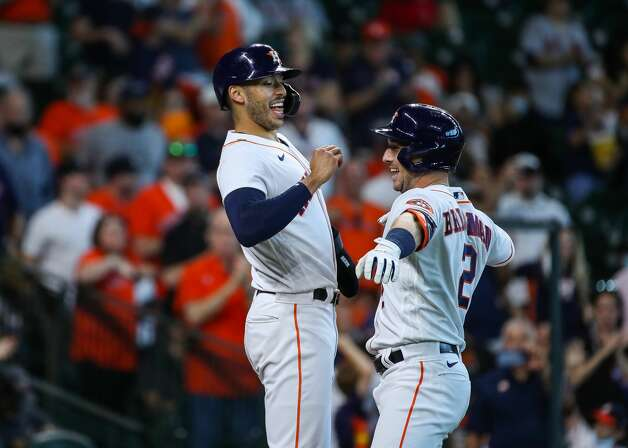 Houston Astros third baseman Alex Bregman (2) celebrates with shortstop Carlos Correa (1) after hitting a three-run home run against the Los Angeles Angels during the third inning of an MLB game at Minute Maid Park on Saturday, April 24, 2021, in Houston. Photo: Godofredo A Vásquez/Staff Photographer / © 2021 Houston Chronicle