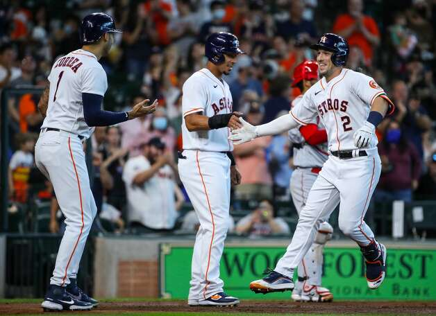 Houston Astros third baseman Alex Bregman (2) celebrates with left fielder Michael Brantley (23), and shortstop Carlos Correa (1) after hitting a three-run home run against the Los Angeles Angels during the third inning of an MLB game at Minute Maid Park on Saturday, April 24, 2021, in Houston. Photo: Godofredo A Vásquez/Staff Photographer / © 2021 Houston Chronicle
