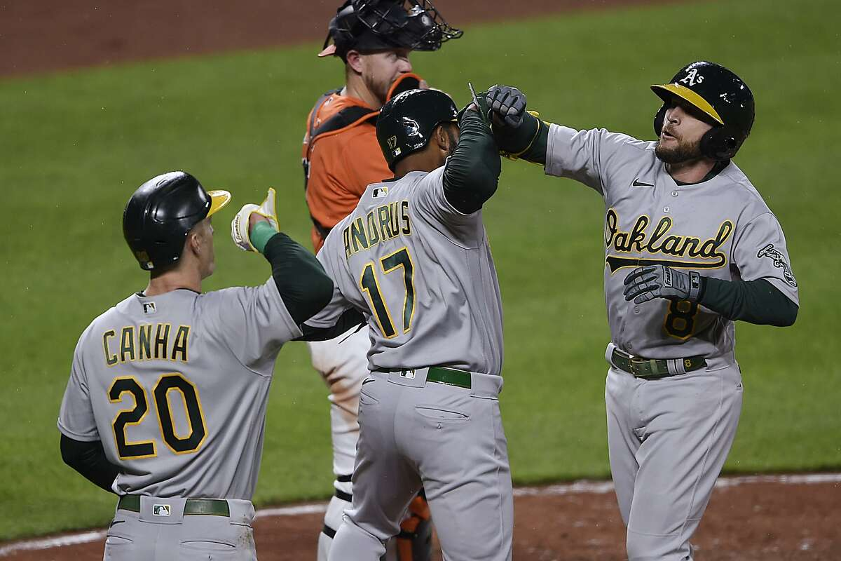 Oakland's Jed Lowrie (right) celebrates his three-run home run with Elvis Andrus (17) and Mark Canha (20) in the fourth inning at Camden Yards.