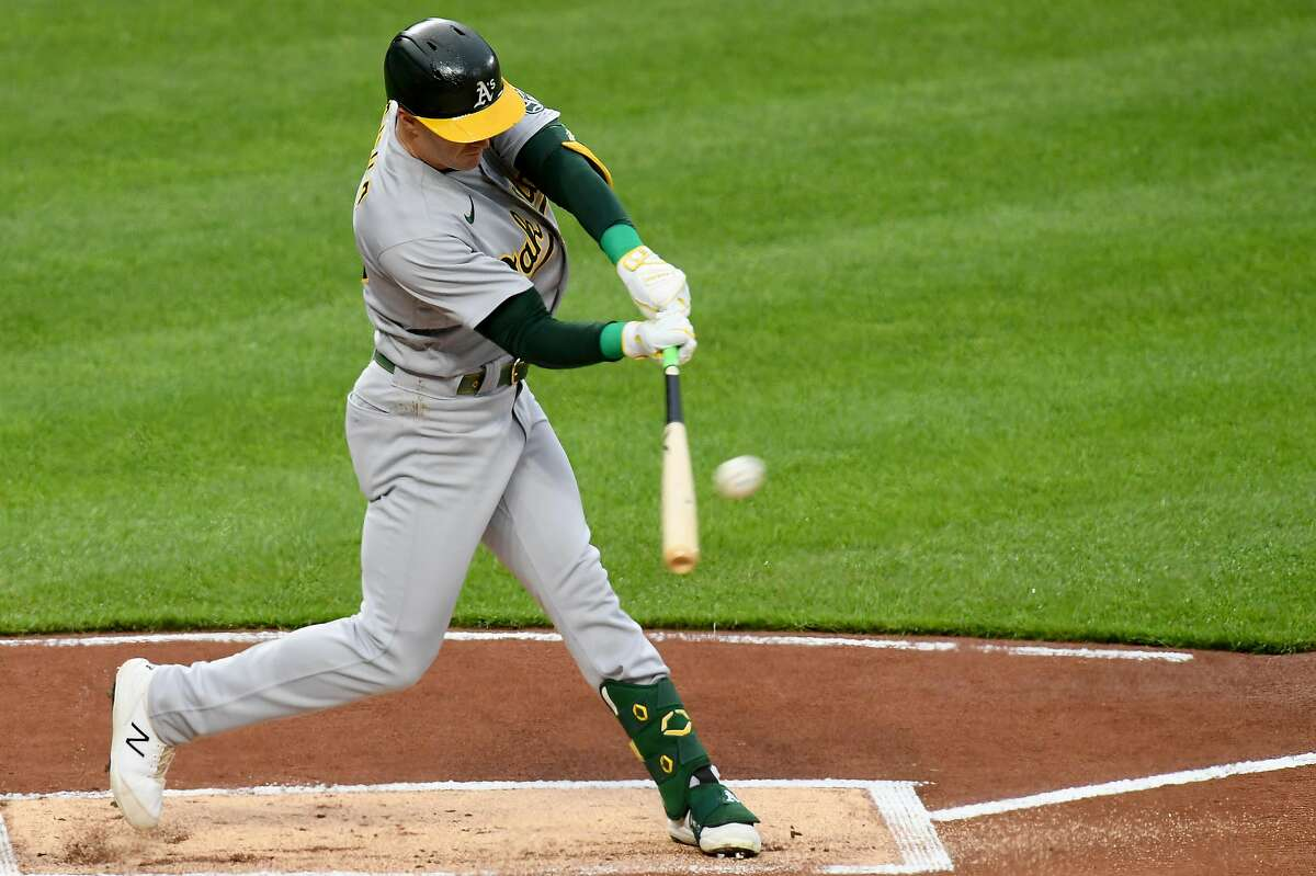 BALTIMORE, MARYLAND - APRIL 24: Mark Canha #20 of the Oakland Athletics hits a double against the Baltimore Orioles during the first inning at Oriole Park at Camden Yards on April 24, 2021 in Baltimore, Maryland. (Photo by Will Newton/Getty Images)