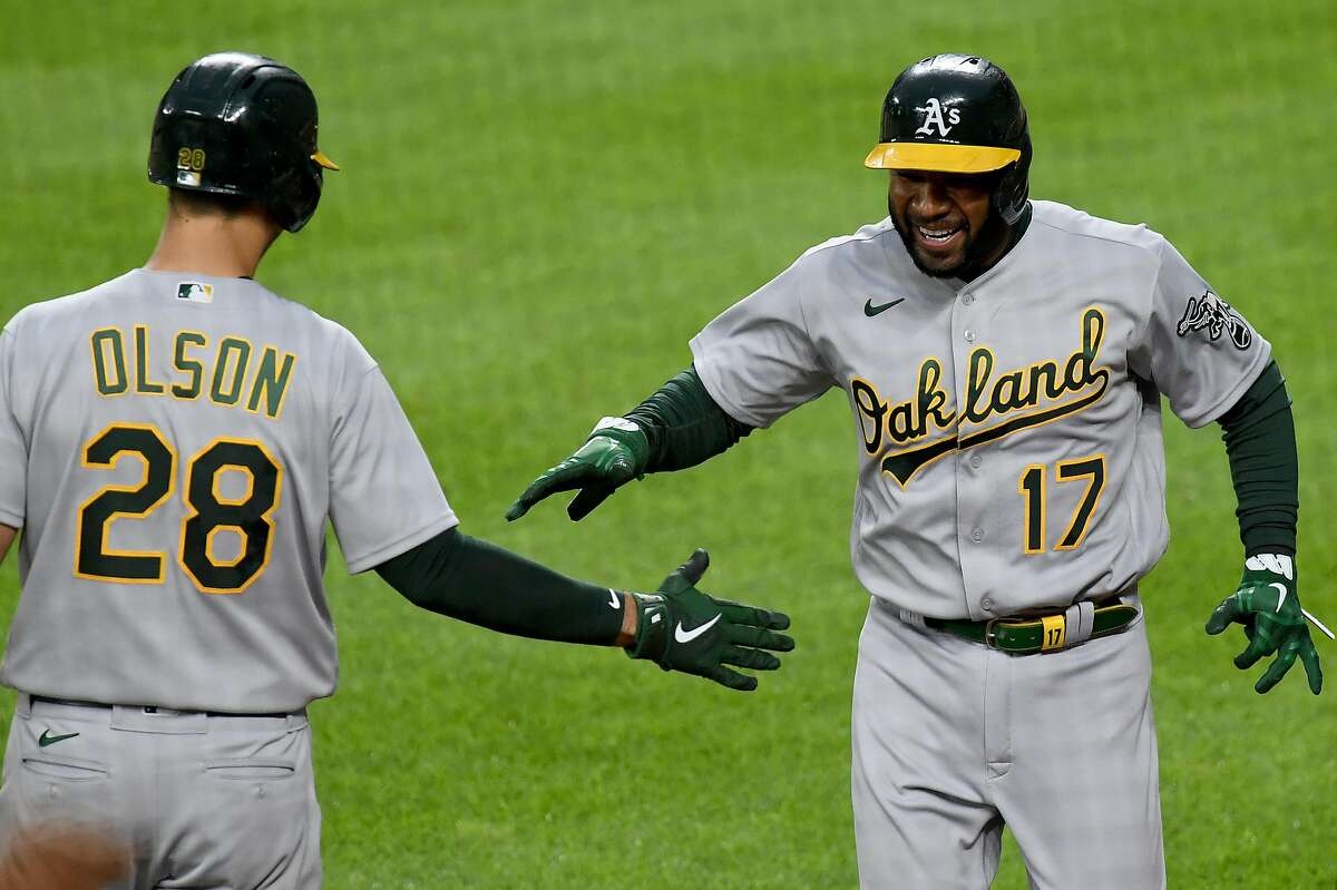 BALTIMORE, MARYLAND - APRIL 24: Elvis Andrus #17 of the Oakland Athletics celebrates with Matt Olson #28 after scoring against the Baltimore Orioles during the second inning at Oriole Park at Camden Yards on April 24, 2021 in Baltimore, Maryland. (Photo by Will Newton/Getty Images)