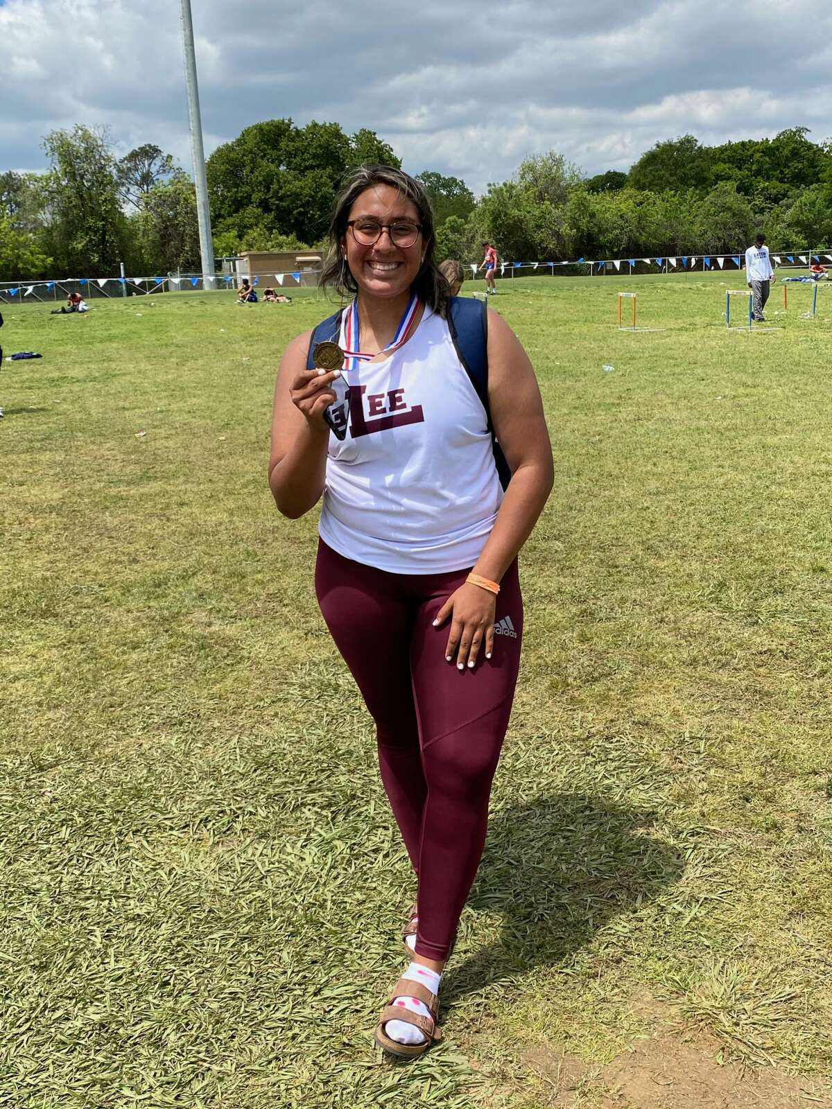 Lee sophomore Leah Acostaposes with her bronze medal after placing third in the girls discus at the Region I-6A track meet, Saturday in Arlington.