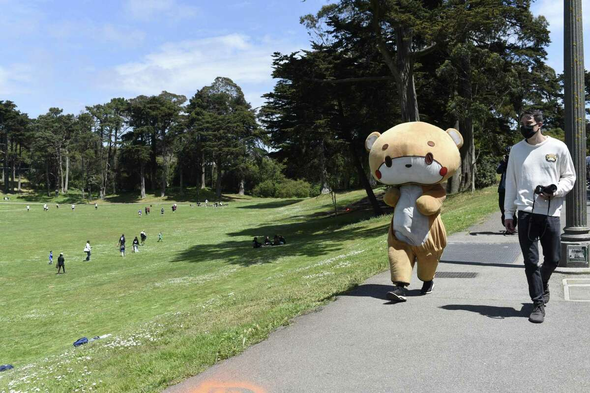 Jesse Larios walks in the suit of his character, Bearsun, in Golden Gate Park.