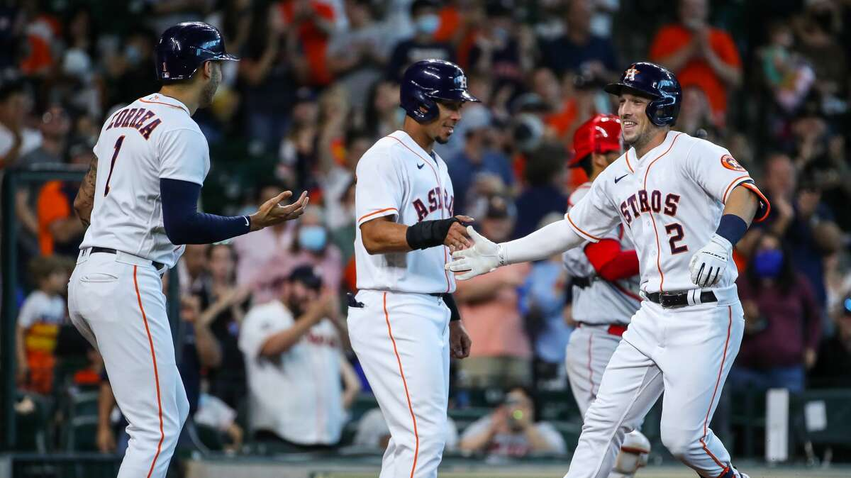 Houston Astros third baseman Alex Bregman (2) celebrates with left fielder Michael Brantley (23), and shortstop Carlos Correa (1) after hitting a three-run home run against the Los Angeles Angels during the third inning of an MLB game at Minute Maid Park on Saturday, April 24, 2021, in Houston.