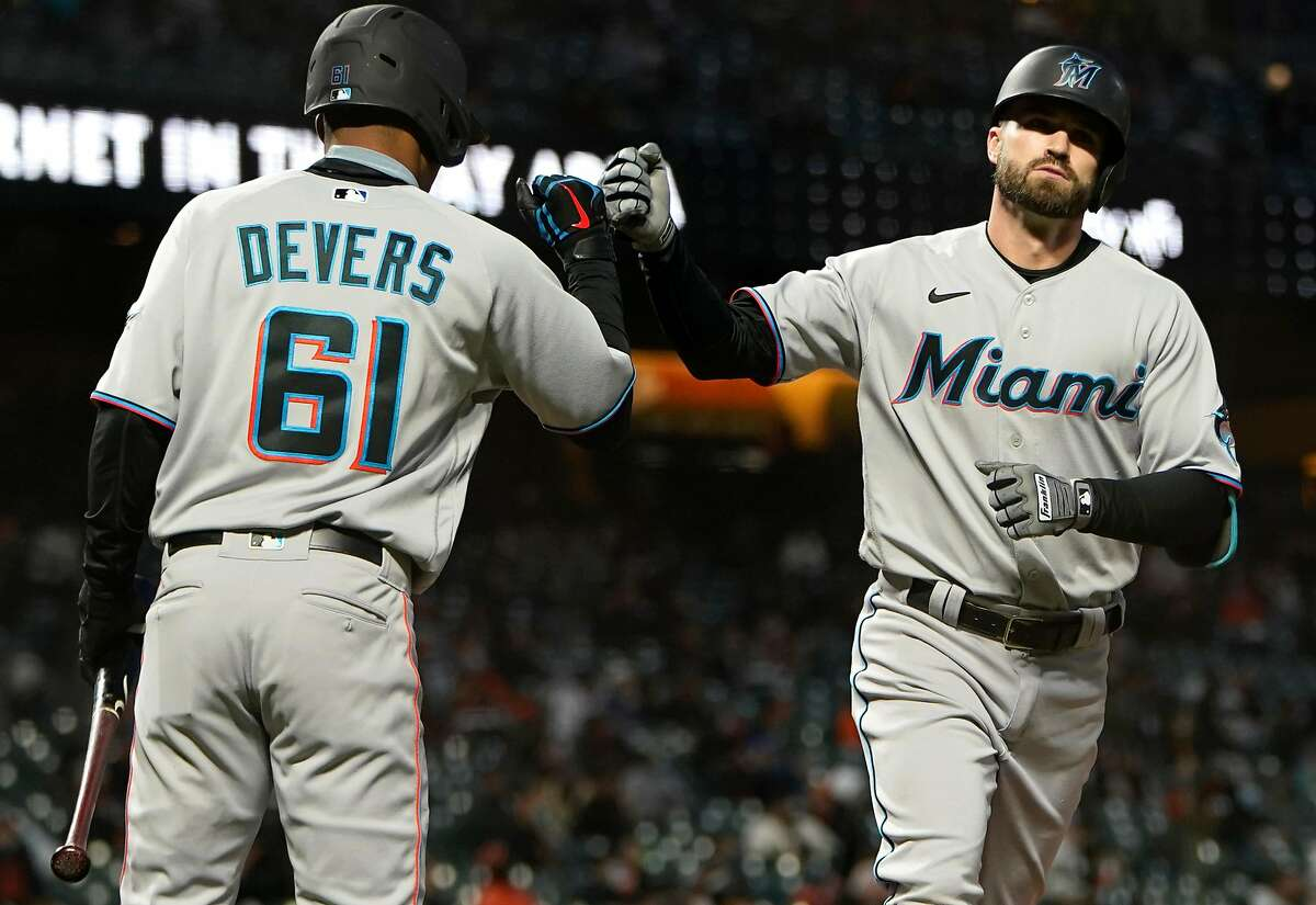 Miami's Jose Devers (61) congratulates Jon Berti after his solo home run tied the game in the seventh inning.