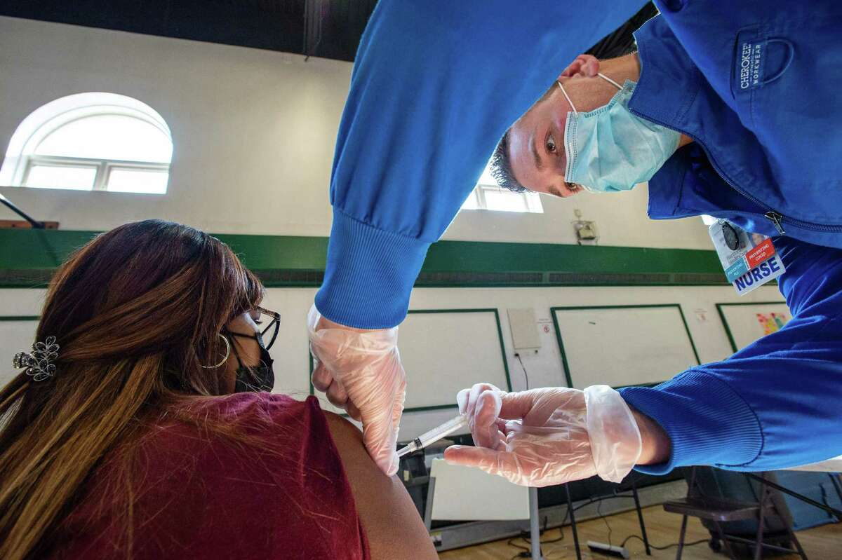 Sucre Lopez receives her second dose of the Moderna Covid-19 vaccine from registered nurse Frederick Morley at a mobile Covid-19 vaccination clinic at Saint Charles Borromeo Catholic Church's McGivney community center in Bridgeport, Connecticut on April 20, 2021.