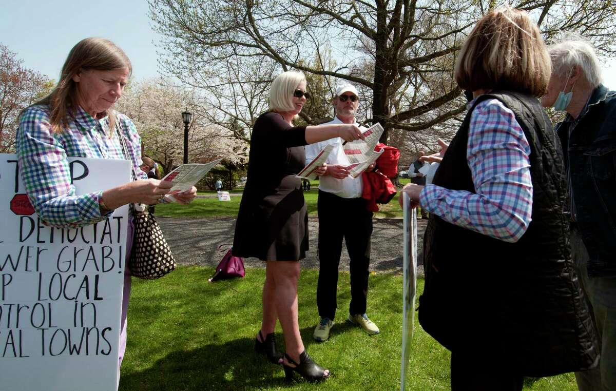 Alexis Harrison, of Fairfield, center, hands out flyers to promote CT 169 Strong at Ballard Park in Ridgefield, Conn., on Saturday April 24, 2021.
