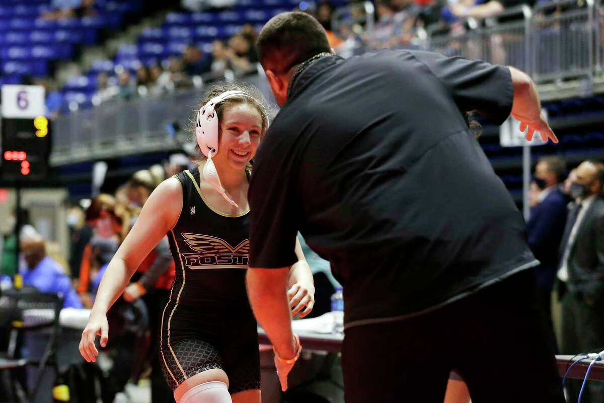 Madison Canales with Richmond Foster, left, goes to hug her coach after winning in the Third place 119 weight class of the UIL Girls 5A State Wrestling Championships Friday, Apr. 23, 2021 at the Berry Center in Cypress, TX.