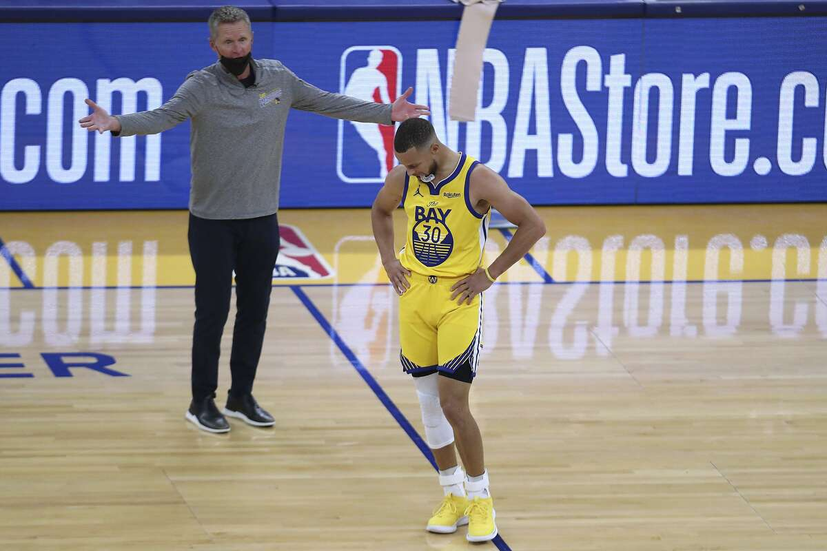 Golden State Warriors' Stephen Curry, right, reacts to a foul call as coach Steve Kerr questions the call during the first half of the team's NBA basketball game against the Denver Nuggets in San Francisco, Friday, April 23, 2021. (AP Photo/Jed Jacobsohn)