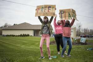 From left, Jefferson Middle School students Katherone Potts, 14, Mia Chappell, 14, and Gillian Smith, 12, hold up signs as they work alongside classmates to pass out potted flowers and vegetables to flood victims Saturday, April 24, 2021 at the Islamic Center of Midland. (Katy Kildee/kkildee@mdn.net)