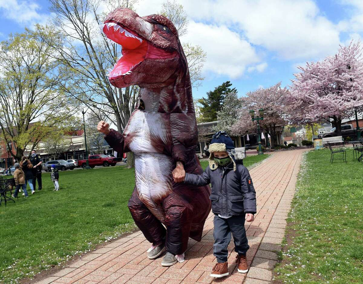 WPLR and WFOX radio personality AJ, dressed as Godzilla, walks across the Branford Green with four-year-old Seth Plourde of Branford on April 22, 2021. The radio stations teamed up with Make-A-Wish Connecticut to raise over $10,000 last week to pay for an RV camping trip down south for Seth and his family. Seth, whose favorite character is Godzilla, was born with a congenital heart defect and has had three open heart surgeries.