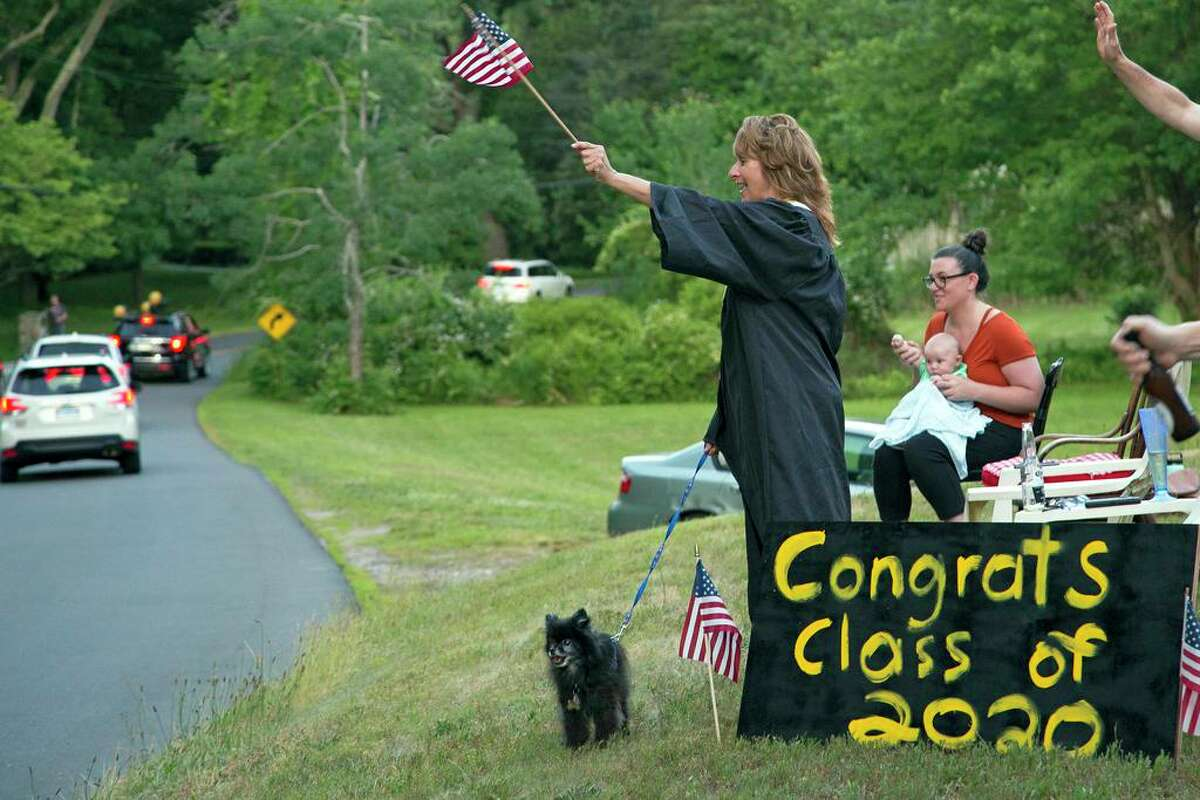 Laurie Davis waves from her front lawn to the passing recessional graduation parade of Daniel Hand High School class of 2020 in Madison, June 18, 2020. Davis said she taught preschool for a long time, so that many of the current high school graduating seniors were likely her former students.