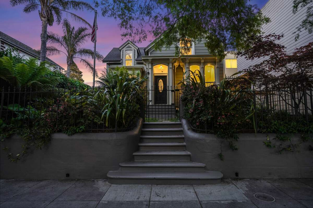 Seen by twilight, this Victorian rests far back on its wide lot.