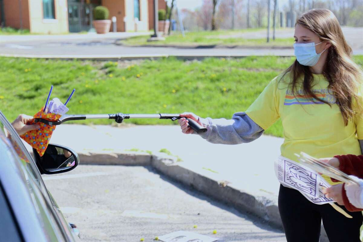 Volunteer Becky Skinner of Quinnipiac University does a safe hand-off at the Best Buddies drive-through event at Staples High School on Saturday, April 24, 2021, in Westport, Conn.