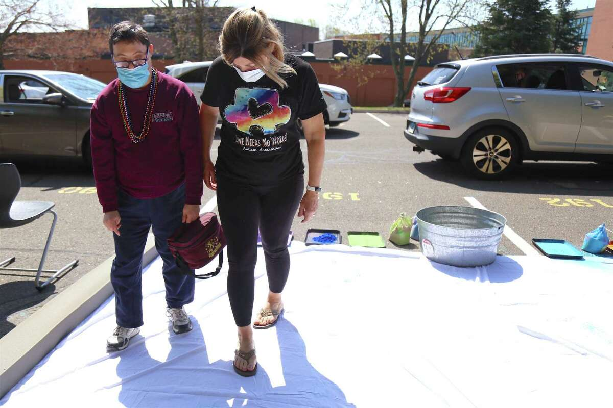 Brad Rowland, of Ansonia, and Karen O'Connor, of Hamden, make their mark at the Best Buddies drive-through event at Staples High School on Saturday, April 24, 2021, in Westport, Conn.
