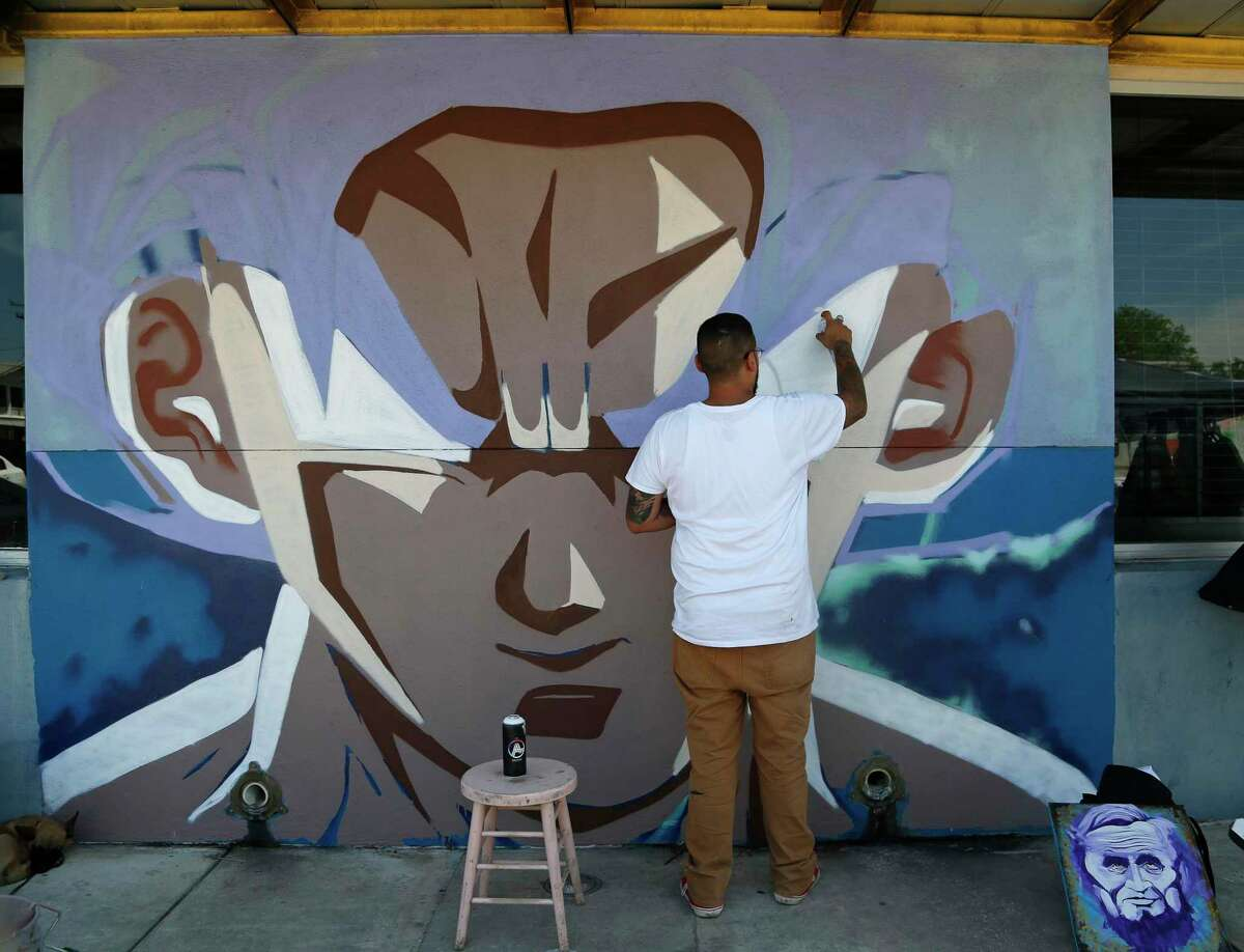 Marco Vargas works on his mural. San Anto Cultural Arts is installing several painted public art murals on the West Side, this one at corner of Zarzamora and West Commerce on Sunday, April 25, 2021.