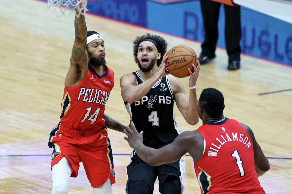 San Antonio Spurs guard Derrick White (4) goes up for a basket as New Orleans Pelicans forward Brandon Ingram (14) and forward Zion Williamson (1) defend in the second half of an NBA basketball game in New Orleans, Saturday, April 24, 2021. (AP Photo/Rusty Costanza)