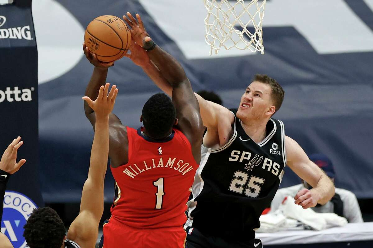 San Antonio Spurs center Jakob Poeltl (25) blocks a shot by New Orleans Pelicans forward Zion Williamson (1) in the second half of an NBA basketball game in New Orleans, Saturday, April 24, 2021. (AP Photo/Rusty Costanza)