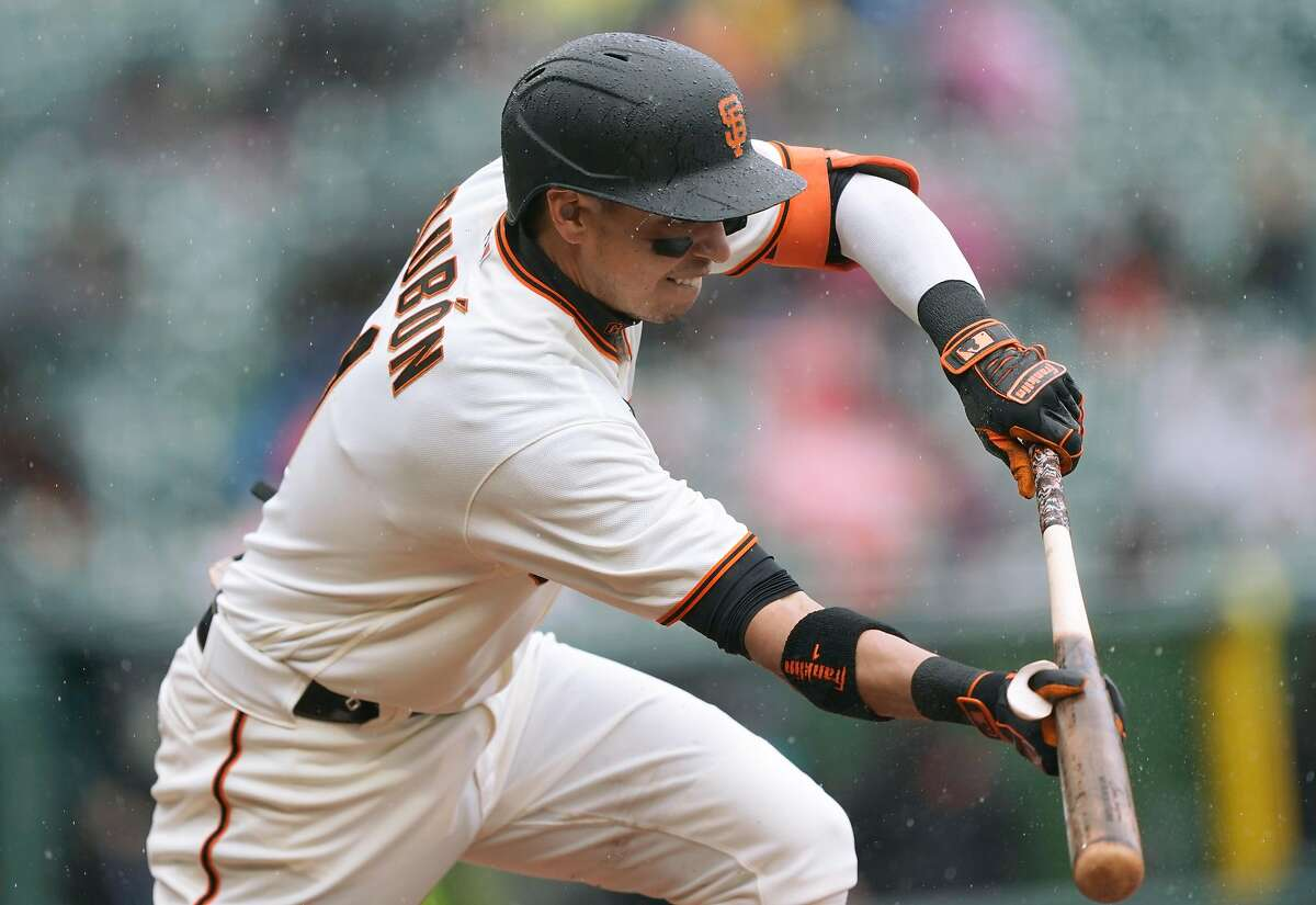 Mauricio Dubon #1 of the San Francisco Giants bunts for an rbi single scoring Wilmer Flores #41 against the Miami Marlins in the second inning at Oracle Park on April 25, 2021 in San Francisco, California.
