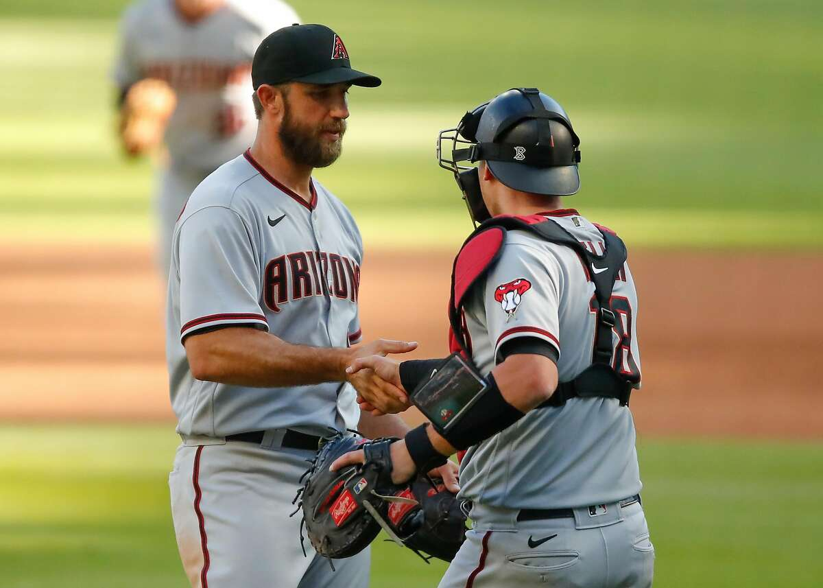 ATLANTA, GA - APRIL 25: Madison Bumgarner #40 reacts with Carson Kelly #18 of the Arizona Diamondbacks at the conclusion of game 2 of a double header against the Atlanta Braves at Truist Park on April 25, 2021 in Atlanta, Georgia. (Photo by Todd Kirkland/Getty Images)