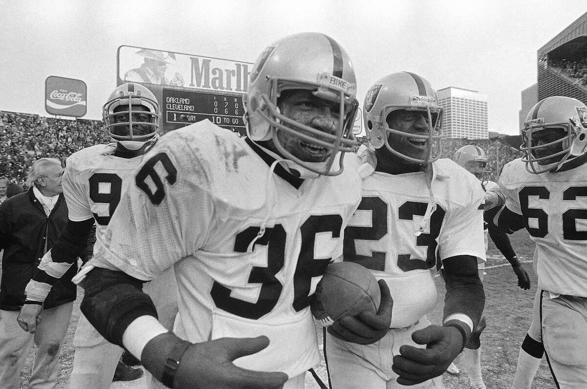 FILE - In this Sunday, Jan. 5, 1981 file photo, Oakland Raiders safety Mike Davis (36) runs off the field with the ball after intercepting a pass from Cleveland Browns quarterback Brian Sipe in the end zone with a few seconds left in AFC playoff football game in Cleveland. Mike Davis, the former Raiders defensive back who made one of the most memorable interceptions in team history, has died, Sunday, April 25, 2021. He was 65. (AP Photo/Brian Horton, File)