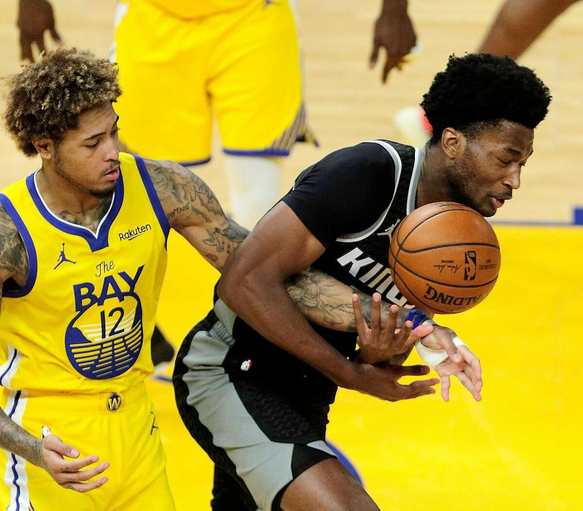Kelly Oubre Jr. (12) pokes the ball away from Damian Jones (15) in the third quarter as the Golden State Warriors played the Sacramento Kings at Chase Center in San Francisco Calif., on Sunday, April 25, 2021.