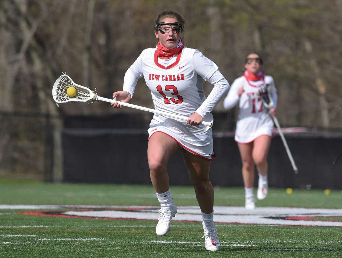 New Canaan's McKenna Harden (13) races through the midfield against Darien during a girls lacrosse game at Dunning Field in April.