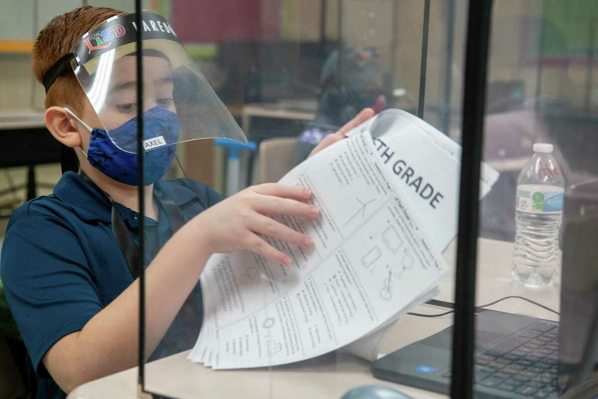 Students in Lorena Acosta's 5th grade classroom use masks, face shields and desk shields to work on their chromebooks alongside their remote-only classmates.