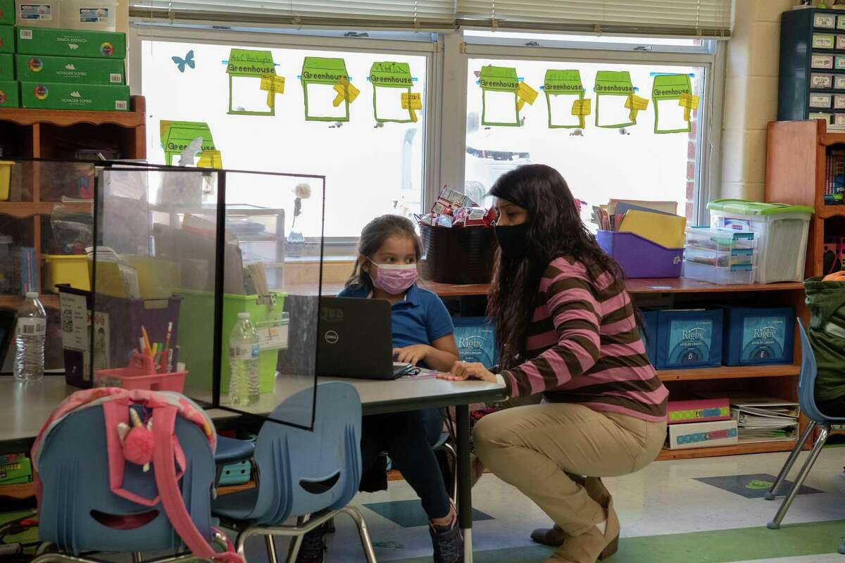 Kinder teacher Claudia Huntington monitors and helps her kindergarten students as they work on their devices before their asynchronous learning period.