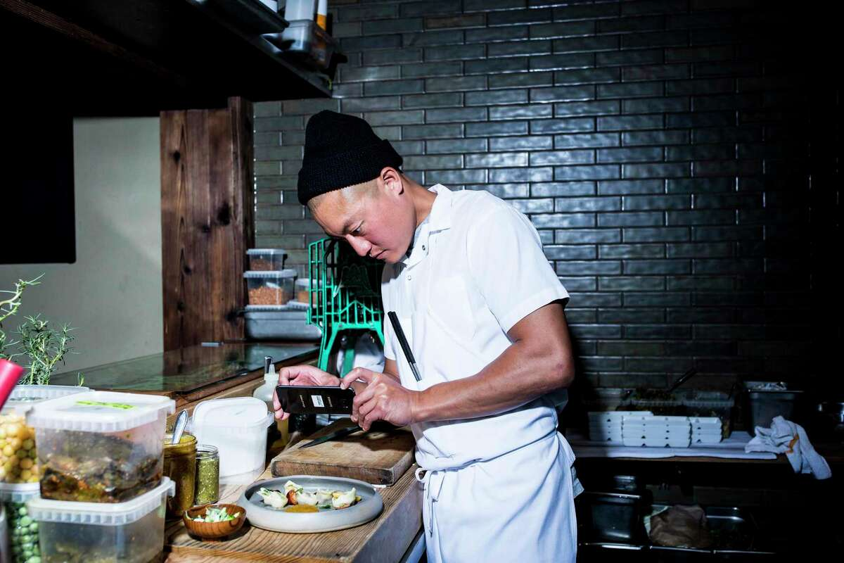 Chef Dennis Lee of Namu Gaji photographs a completed dish during dinner service in S.F.