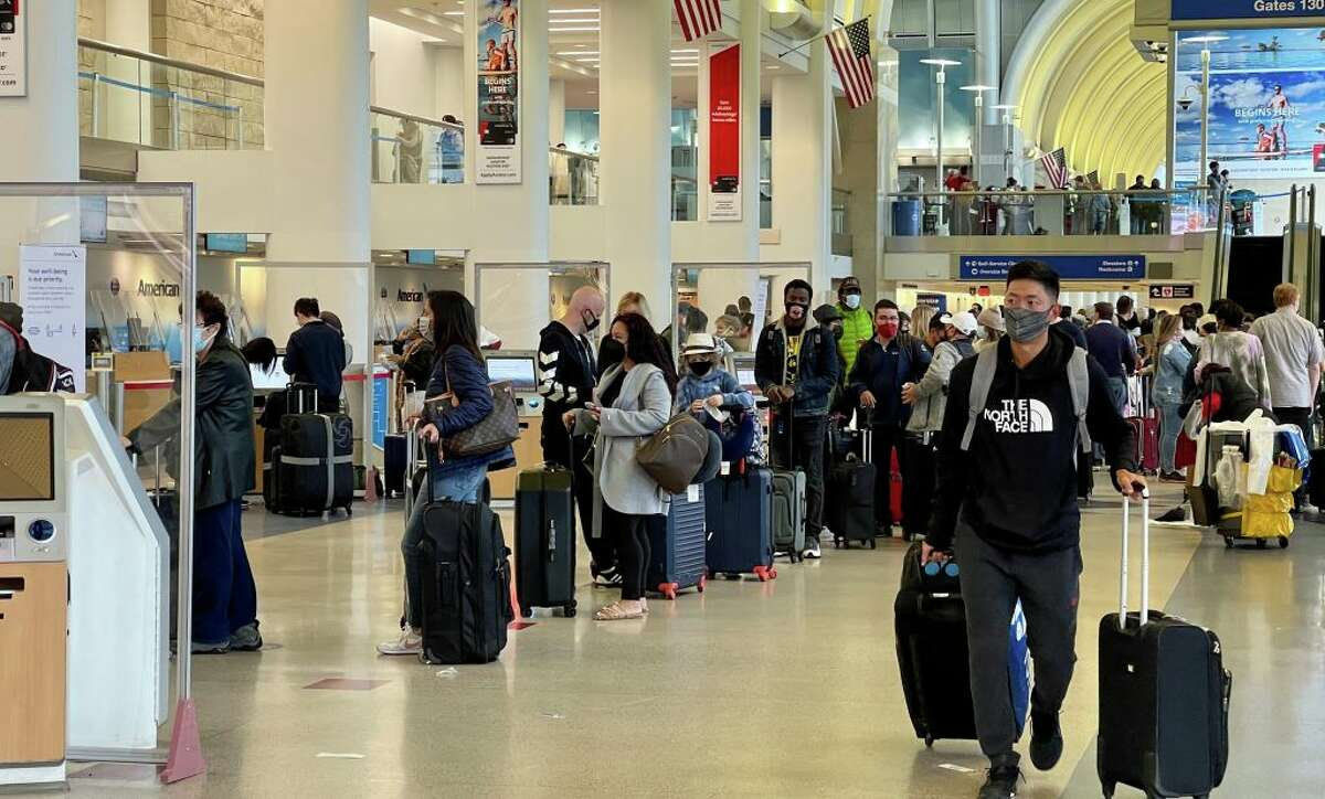 Passengers wait in line at the American Airlines check-in counters at the Los Angeles International Airport (LAX) on April 24, 2021.
