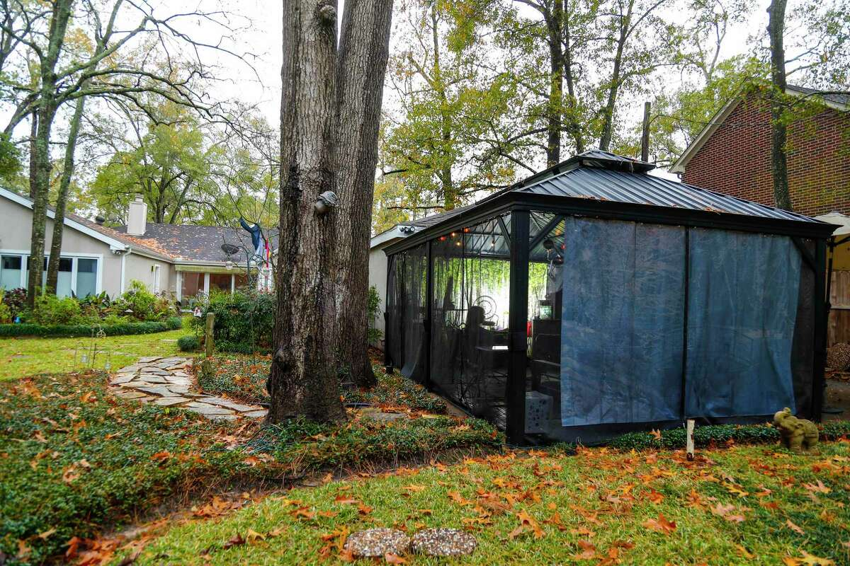 """Sharon Brier and her husband, 's outdoor gazebo/patio room, Wednesday, December 30, 2020, in Houston. She and her husband created after the pandemic started, and she keeps a refrigerator there, created a backdrop to """"hide"""" the garage and has added other things so she can sit out there with friends safely during the pandemic."""
