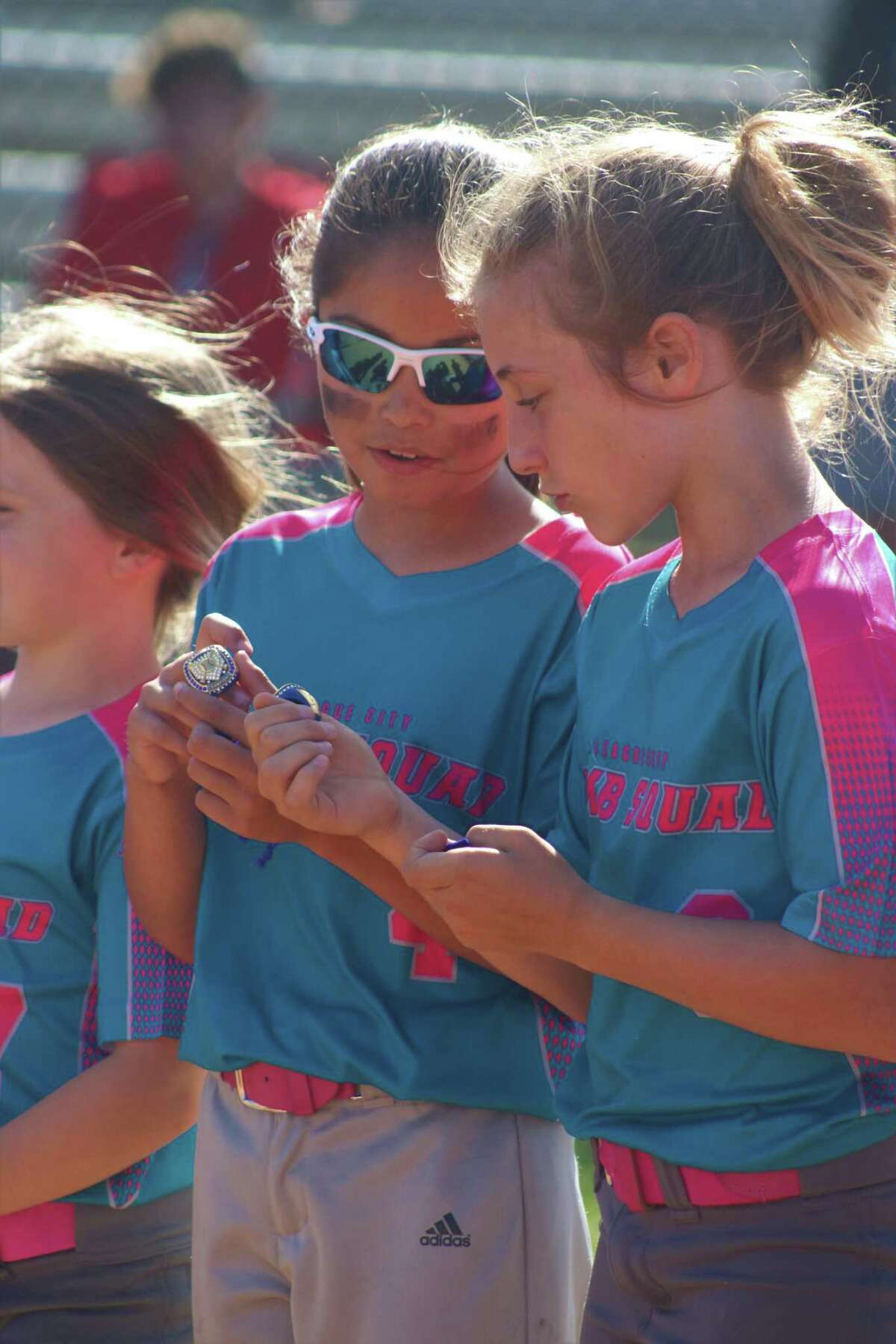 The Bomb Squad's Natalie Gammon (left) and Riley Loynes compare tournament championship rings during ceremonies after the team's 5-2 win Sunday.