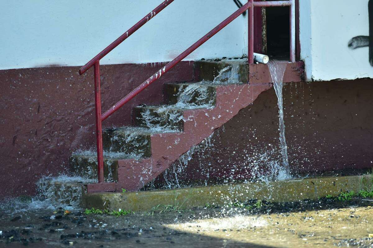 Water pours out of a building Sunday at the former Lone Star Brewery complex.