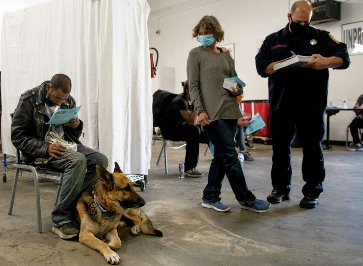 """""""Happy"""" and his dog King wait for 15 minutes after receiving the Johnson and Johnson vaccine at CAM. CAM partnered with the San Antonio Fire Department and Metro Health to provide more than 70 vaccines to the unhoused population from around San Antonio. Outreach workers spent the previous day going out to camp to talk to people and convince them to get vaccinated."""
