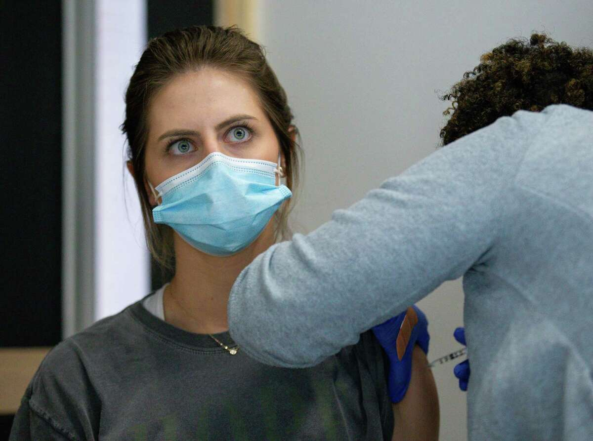 Kaylie Huizenga, 24, gets the first dose of the Pfizer COVID-19 vaccine at Rice University's Bioscience Research Collaborative building on Monday, March 29, 2021, in Houston.