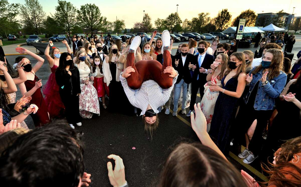 Surrounded by his fellow graduating classmates, Owen Kaufmann does a flip during the Edwardsville High School Parking Lot Prom. Due to the pandemic, the EHS prom was held in the school's parking lot. Only seniors and graduating juniors could attend.