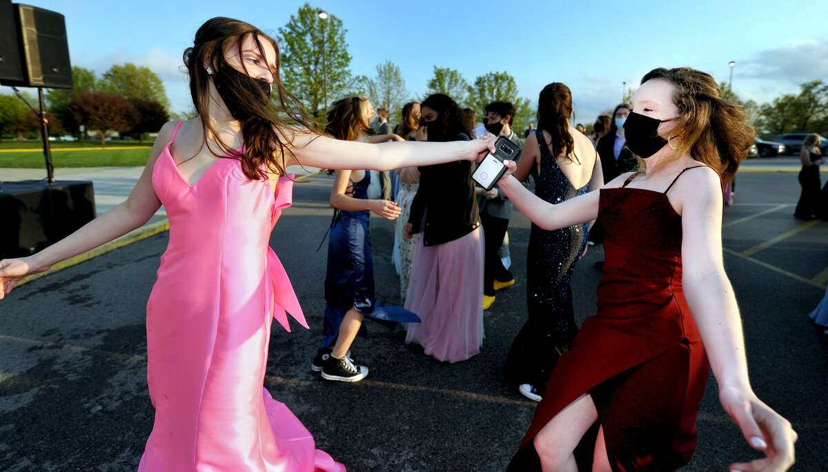 Sophie Jobe (left) and Emily Amick dance in the parking lot at Edwardsville High School Saturday during prom.