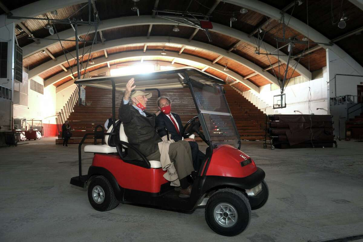 John Phelan, left, who worked as an architect to help design Alumni Hall, sits in a golf cart with Fairfield University President Mark Nemec as they join others for a final tour of the building in Fairfield, Conn. April 26, 2021. Built in 1959, demolition of the hall began Monday morning.