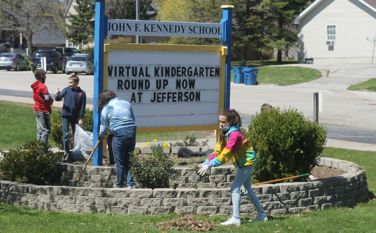 Students in Tanya Hunter's fifth grade class tidy up the front of Kennedy Elementary school last week as part of an Earth Day project. The students will plant flowers, spread grass seed and add new mulch this week to complete the project.
