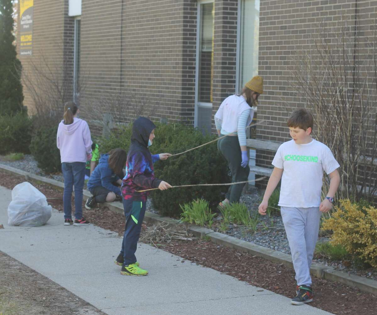 Students in Tanya Hunter's fifth grade class clean out a mulch bed at Kennedy Elementary School as part of an Earth Day project.