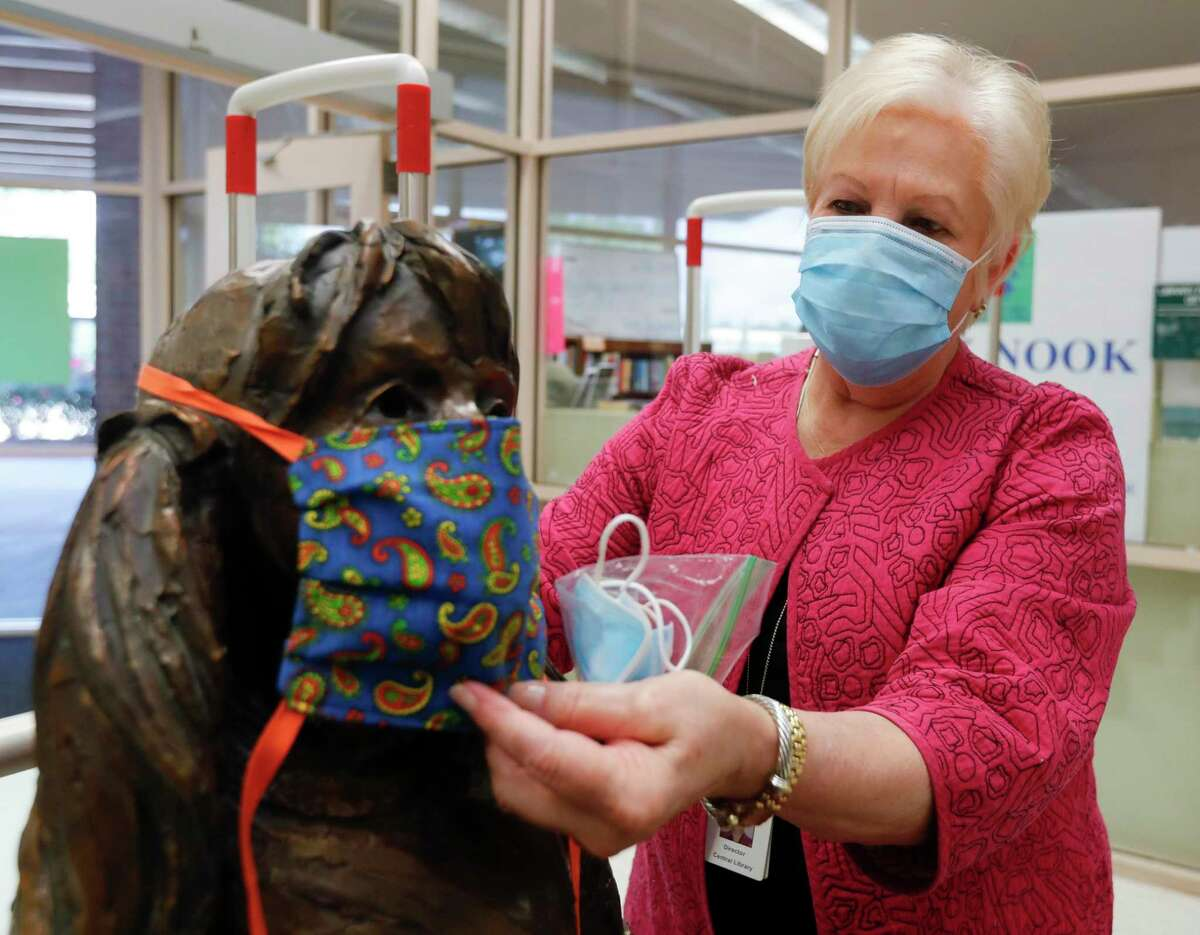 Montgomery County Library Director Jerilynn Williams puts a face mask on the statue near the enterance as staff reopened the Montgomery County Central Library to the public, Wednesday, May 13, 2020, in Conroe.