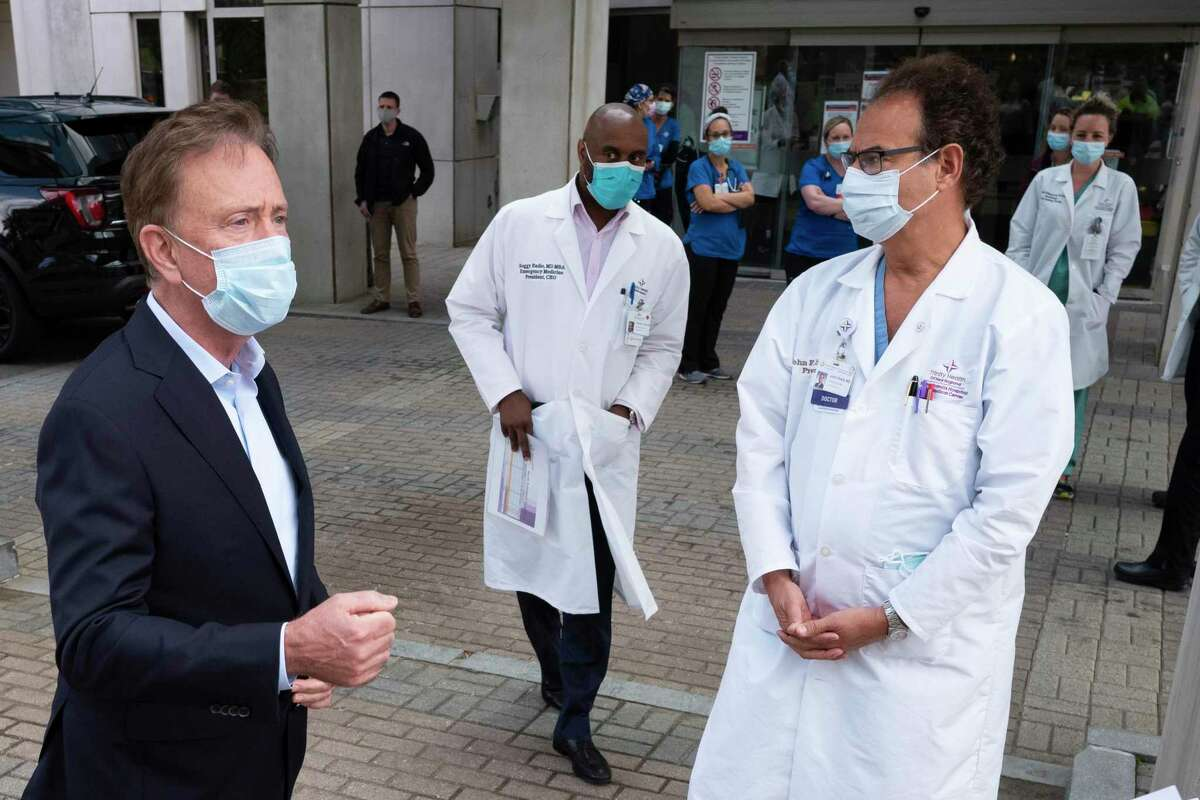 Gov. Ned Lamont, left, talked with medical staff outside Saint Francis Hospital in a May, 2020 file photo.