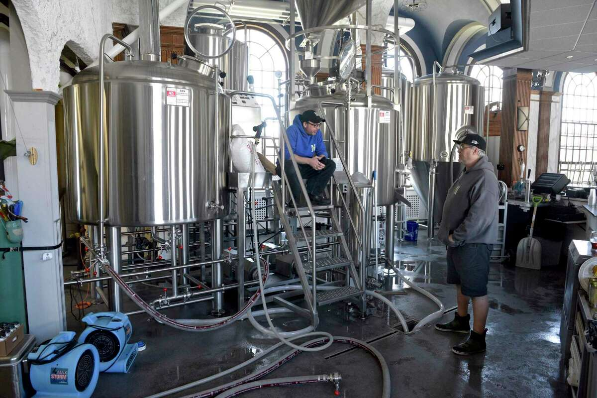 John Watson, right, brewer, and Dave Linari, assistant brewer finish off a batch at NewSylum Brewing Co., on the Fairfield Hill Campus in Newtown, Conn. They were brewing Therapy Session Pale Ale, on Monday, April 26, 2021.