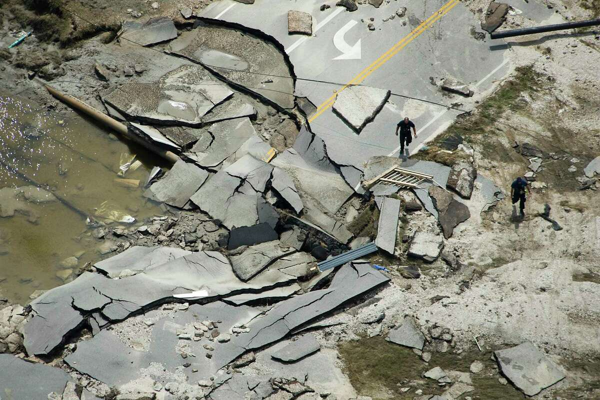 Workers walk through rubble that was left of Texas 87 on the Bolivar Penninsula after Hurricane Ike, Monday, Sept. 15, 2008.