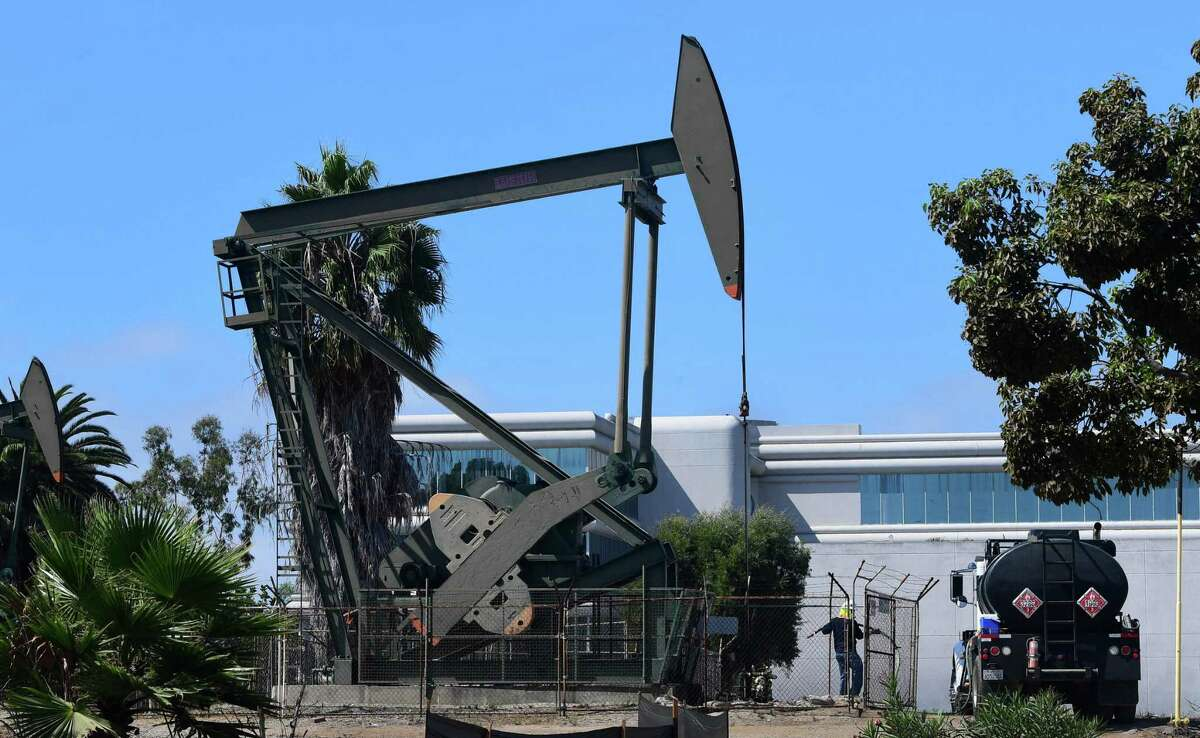 An oil worker pulls a line from a pumpjack in an oil well in Signal Hill, south of Los Angeles, , where oil has been pumped since the 1920s.