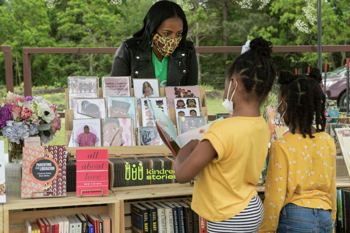 Terri Hamm helps sisters Noele and Taylor Harris on April 18 at Kindred Stories, a pop-up bookstore at Ivy Leaf Farms in Sunnyside.