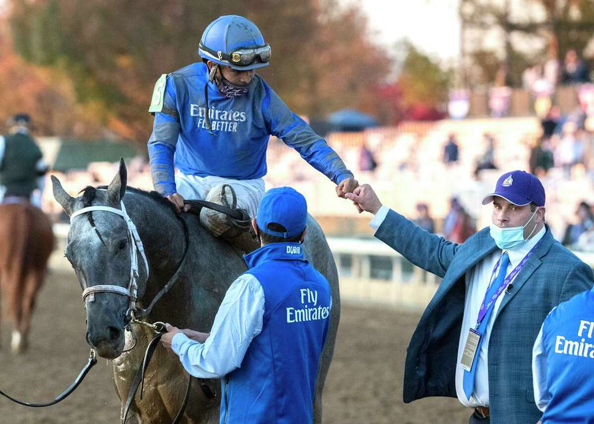 Jockey Luis Saez is congratulated by trainer Brad Cox after winning the $2 million Breeders' Cup Juvenile on Essential Quality in November. Cox is making his Kentucky Derby debut Saturday with Essential Quality.
